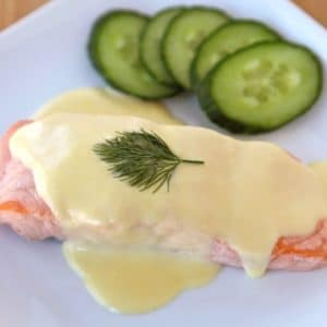 Salmon Mousseline on a white plate with sprig of dill and cucumber salad on the side.