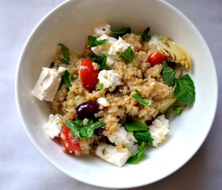 Greek Infused Quinoa Salad - A gluten free vegetarian salad with quinoa for protein, fresh oregano, olives, tomatoes, artichokes and lemon zest. Kosher for Passover, dairy.