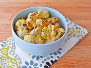 Bowl of roasted cauliflower florets on decorative towels on wooden cutting board.