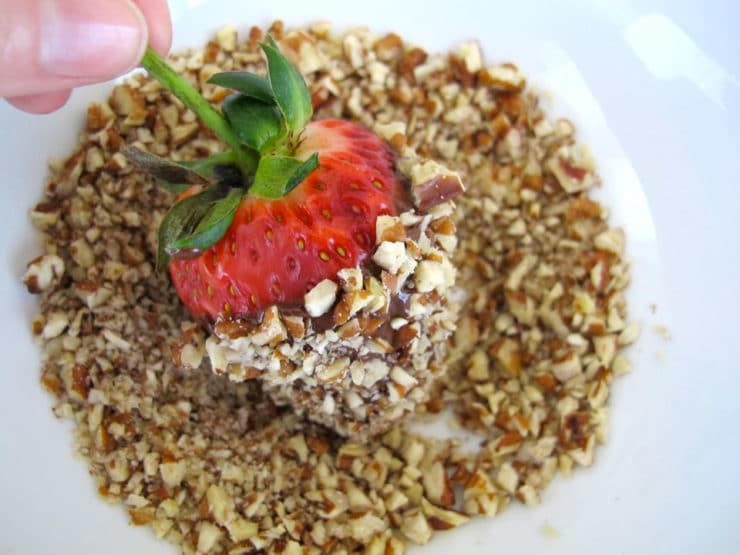 Rolling dipped strawberry in chopped nuts.