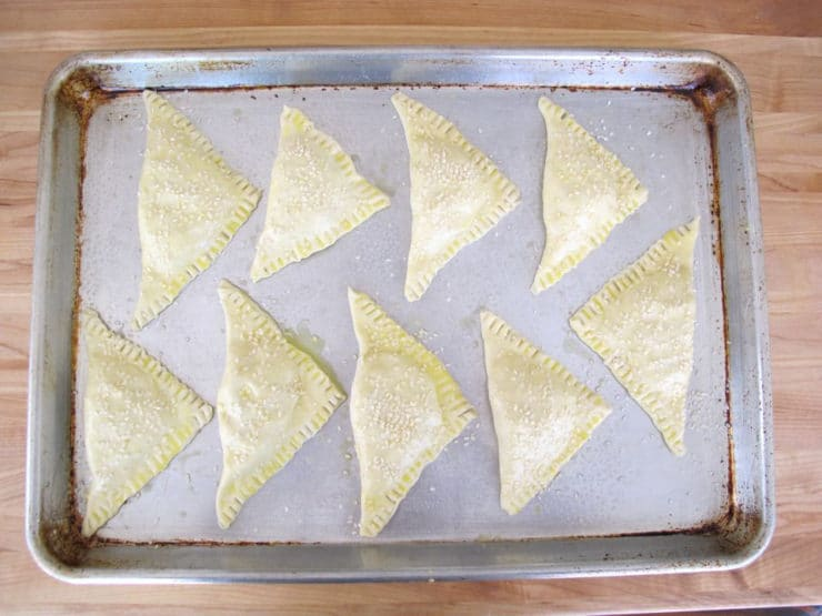 Bourekas on a parchment lined baking sheet.