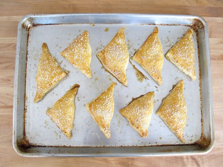 Baked Bourekas on a parchment lined baking sheet.