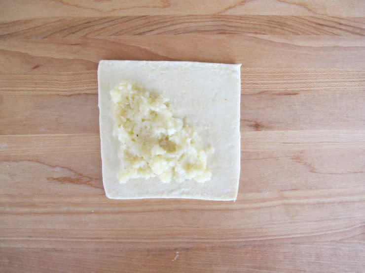 Mashed potato filling on puff pastry square.