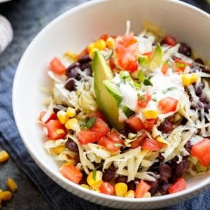 Overhead shot of Quinoa Black Bean Burrito Bowl with avocado, shredded cheese and tomatoes.