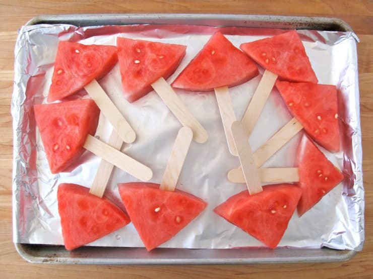 Watermelon pops on foil lined baking sheet.
