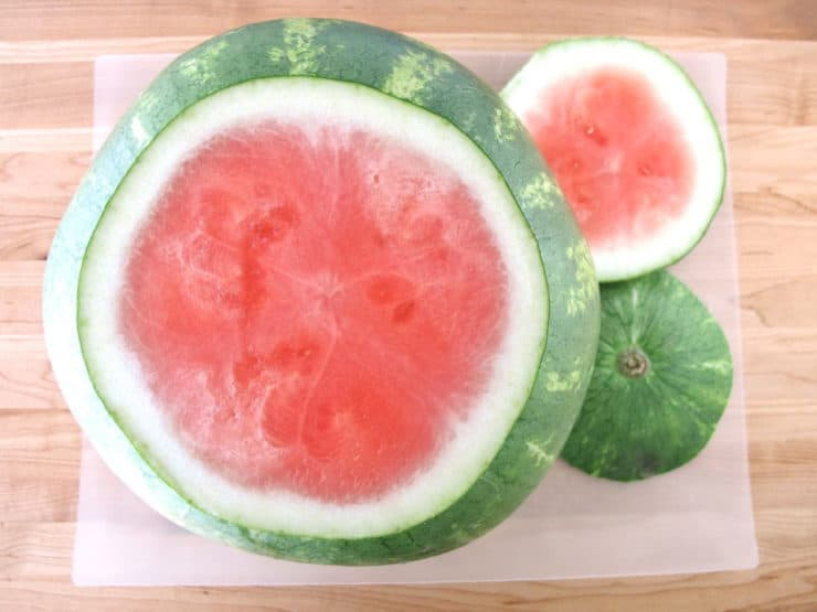 Slicing the ends off a seedless watermelon.