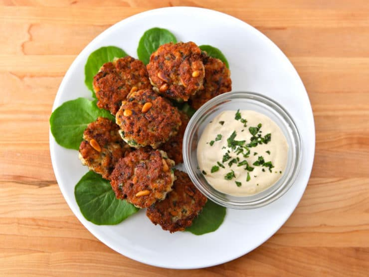 Israeli-Style Fish Cakes - Seasoned fishcakes, known in Israel as ktzitzot dagim. Fried fish patties with pine nuts, breadcrumbs, & seasonings served with tahini sauce.