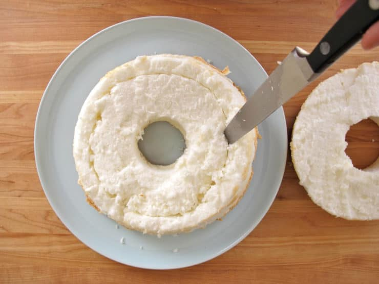Cutting out a center ring of angel food cake.