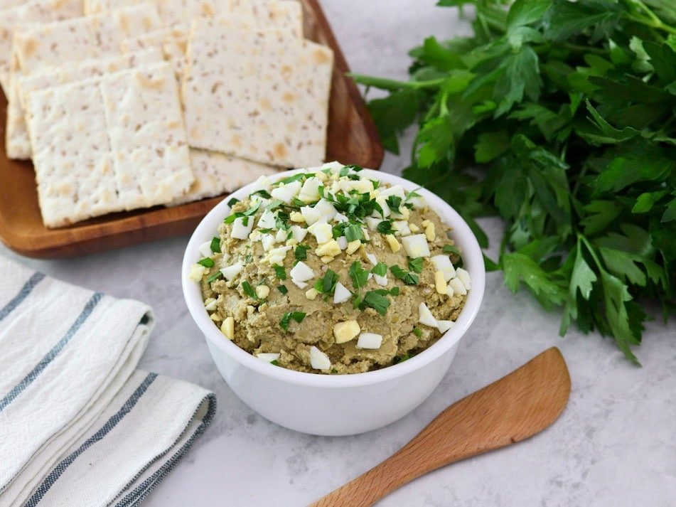 Overhead horizontal shot - White bowl of vegetarian chopped liver topped with chopped hard boiled egg and chopped parsley, with a wooden spatula, bunch of fresh parsley, wooden platter of crackers, and linen napkins beside it, on a marble countertop.