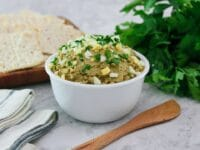 Horizontal shot - White bowl of vegetarian chopped liver topped with chopped hard boiled egg and chopped parsley, with a wooden spatula, bunch of fresh parsley, wooden platter of crackers, and linen napkins beside it, on a marble countertop.