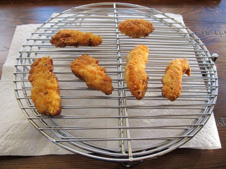 Fried chicken tenders draining on a rack.