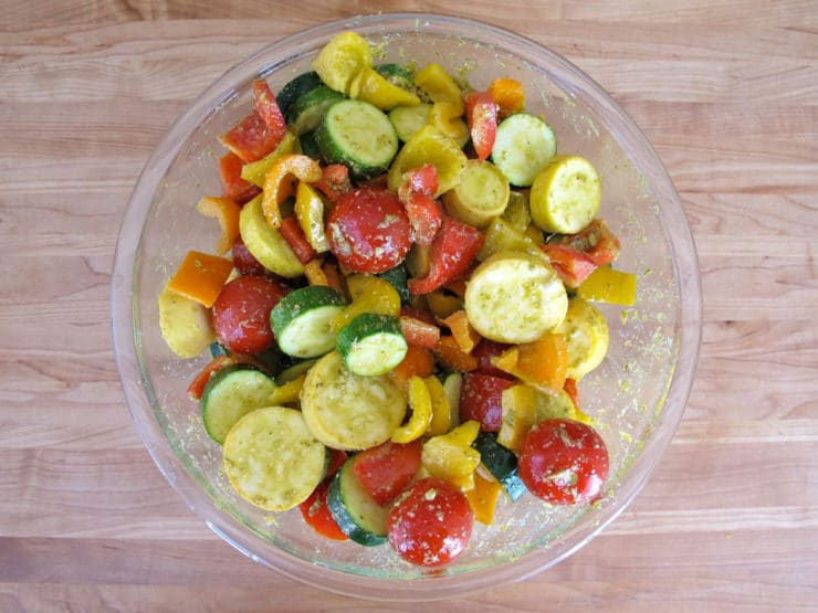 Tossing sliced vegetables in pesto.