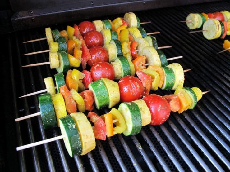 Four lemon pesto vegetable skewers grilling on smoky outdoor barbecue grill.