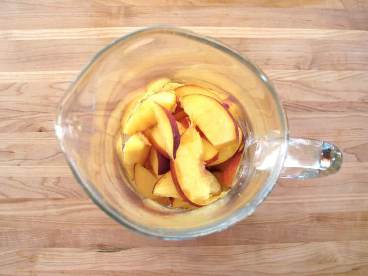 Sliced peaches in a sangria pitcher.