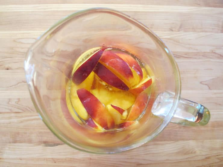 Simple syrup and peaches in a sangria pitcher.