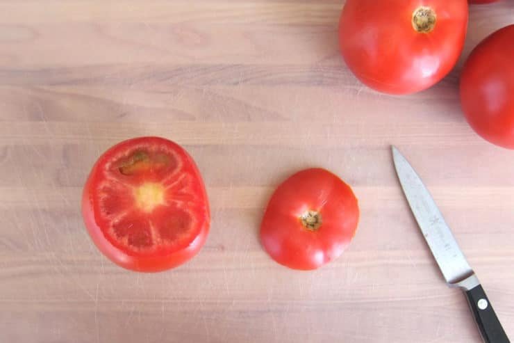 Slicing the tops off tomatoes.