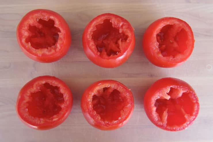 Cored tomatoes on a cutting board.