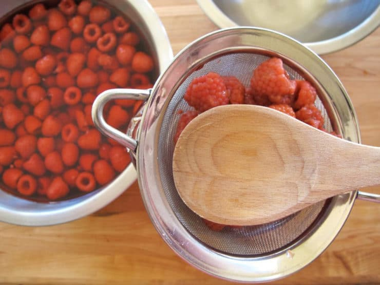 Using a wood spoon to get all liquid out of raspberries.