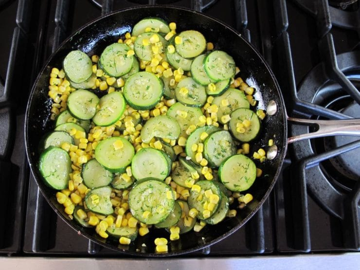 Zucchini rounds in a skillet.