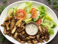 Horizontal image - white platter of chicken shawarma with fresh lettuce and tomato, small dish of tahini in center garnished with sprinkle of parsley, on a brown countertop with fresh parsley beside it.