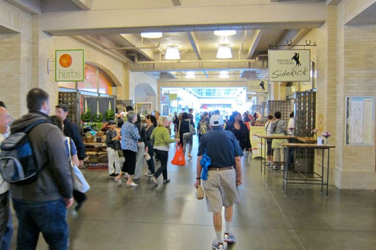 Indoor view of Ferry Plaza Farmer's Market - small crowd of shoppers browsing.