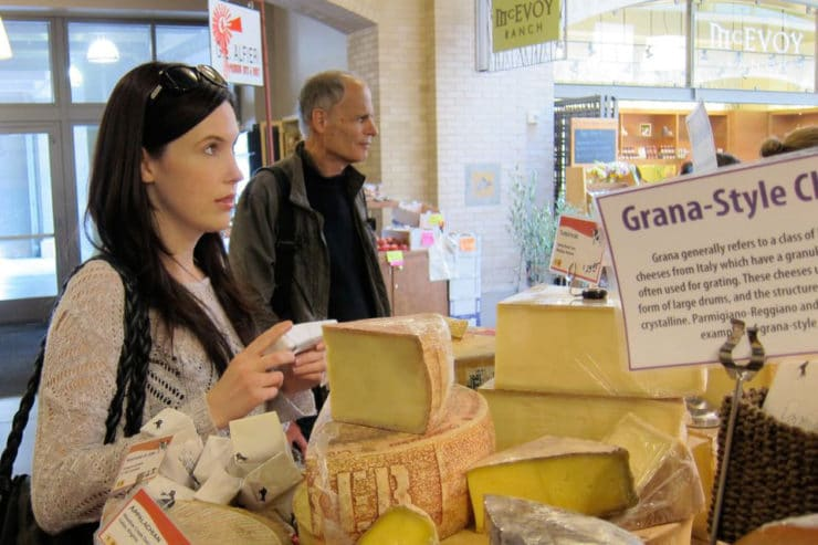 Tori Avey standing at cheese counter at Ferry Plaza Farmer's Market, shopper in background.