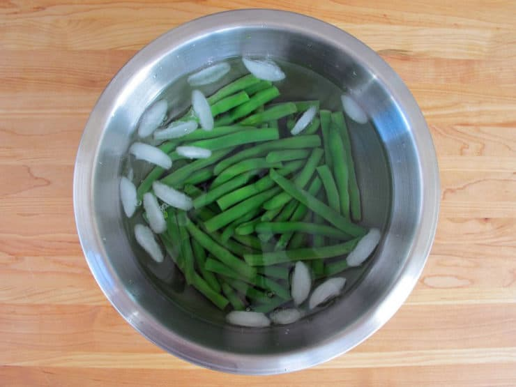 Shocking blanched green beans in ice water.