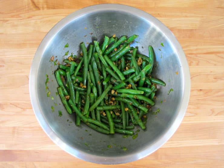 Tossing green beans with dressing in a bowl.