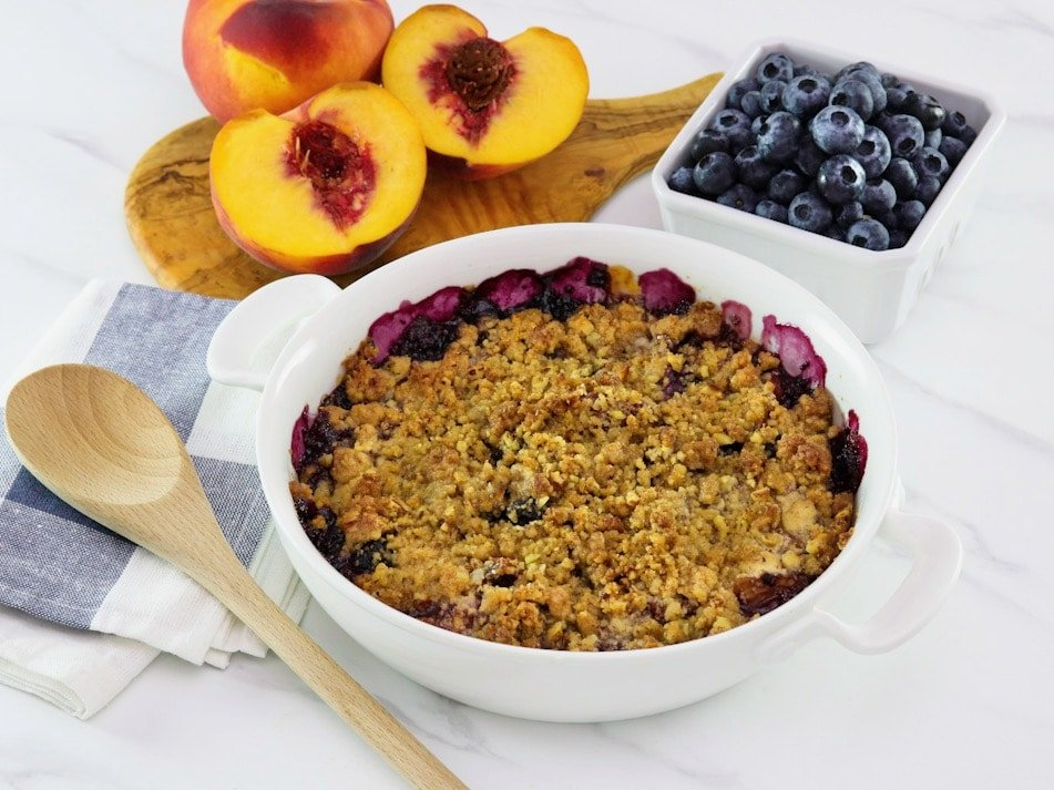 Horizontal image - peach and blueberry crisp in a white baking dish. A wooden spoon is off to the left side and fresh peaches and blueberries are in the background.