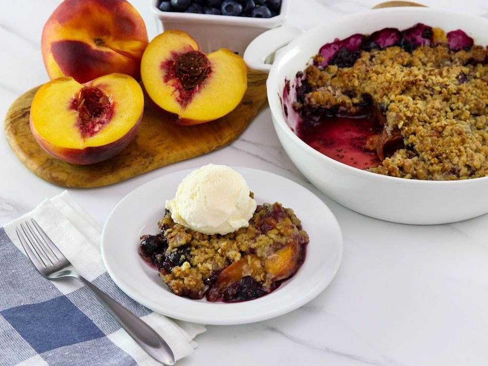 Horizontal image - peach and blueberry crisp on a small white plate, topped with a scoop of vanilla ice cream. A white baking dish of the remaining crisp sits off to the right next to a pile of fresh peaches.