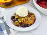 Close-up image - a dish of peach and blueberry crisp topped with a scoop of vanilla ice cream.