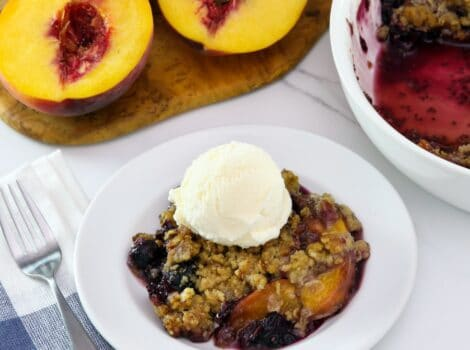 Square image - peach and blueberry crisp on a small white plate, topped with a scoop of vanilla ice cream. A white baking dish of the remaining crisp sits off to the right next to a pile of fresh peaches.