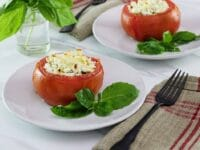Horizontal image - stuffed tomato on a white plate next to fresh basil leaves, a napkin and fork lay to the right side. Another plate, a sprig of basil in a glass of water, and a white towel with red stripes in the background.