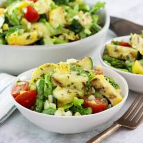 Square image - Two white bowls filled with grilled vegetable salad, a mix of grilled zucchini, squash, asparagus, corn, tomatoes, lettuce and basil with lemony basil dressing. A fork sits off to the right side, a large bowl of the same salad in the background.