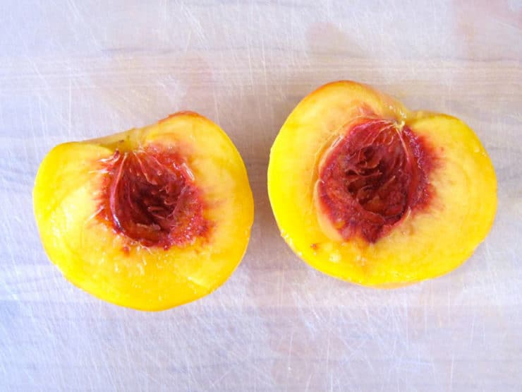 Halved peach on a cutting board.