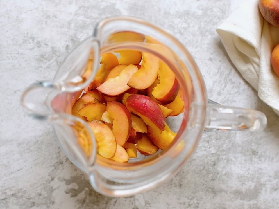 Overhead shot of glass pitcher with sliced peaches sitting at the bottom.