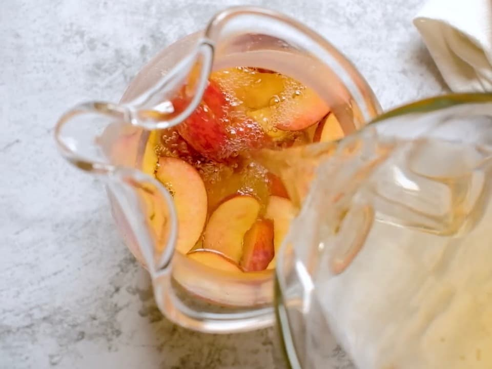 Overhead shot of clear simple syrup being poured into a glass pitcher with sliced peaches at the bottom.