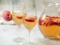Horizontal shot of two wine glasses containing peach sangria and sliced peaches next to a glass pitcher of peach sangria and sliced peaches.