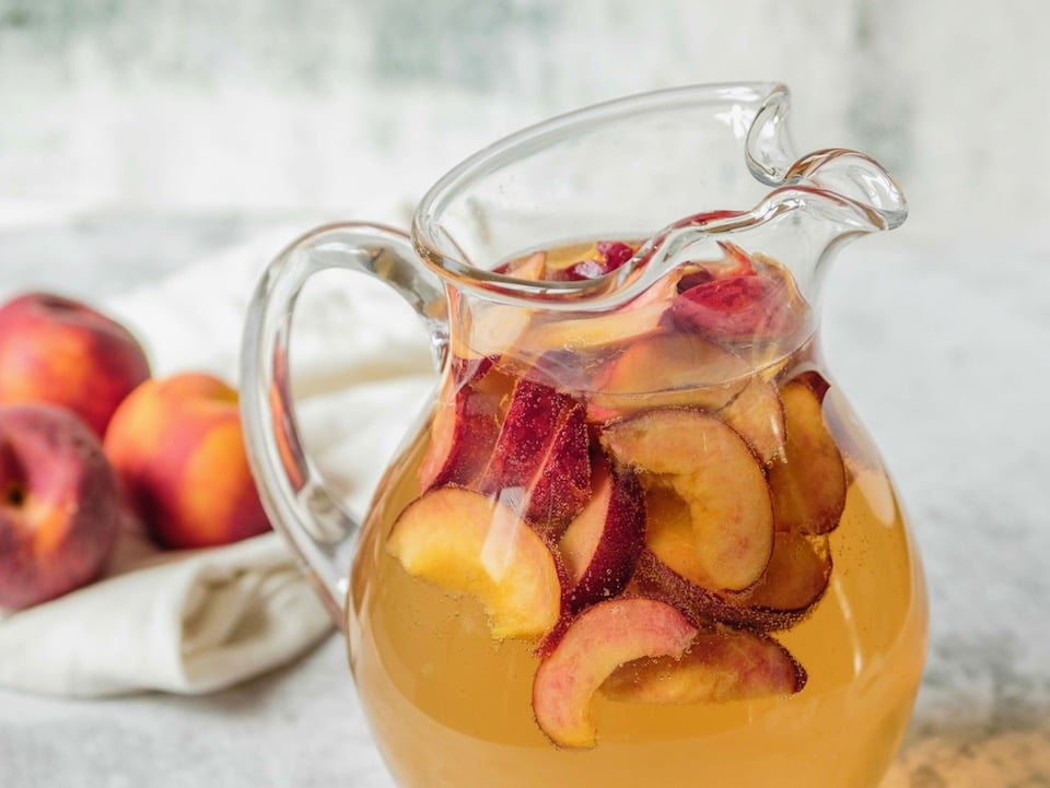 Close up shot of glass pitcher filled with peach sangria and sliced peaches.
