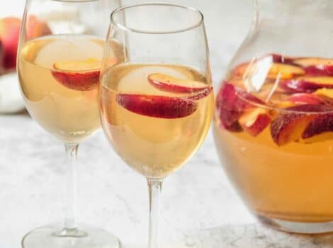 Close up shot of two wine glasses containing peach sangria and sliced peaches next to a glass pitcher of peach sangria and sliced peaches.