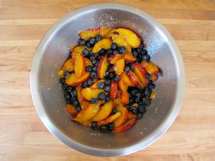 Sliced peaches macerating in a bowl.
