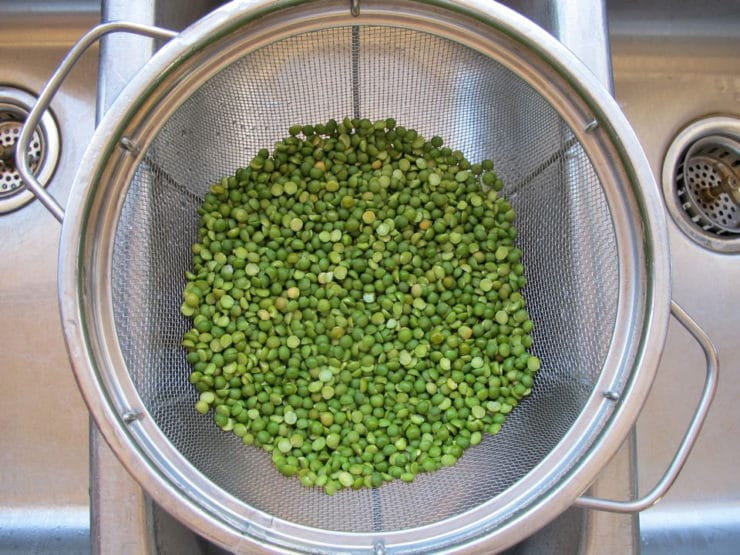 Rinsing split peas in a strainer.