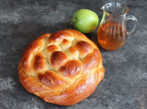 Round braided Apple Honey Challah on concrete background with two green apples and glass carafe of honey.