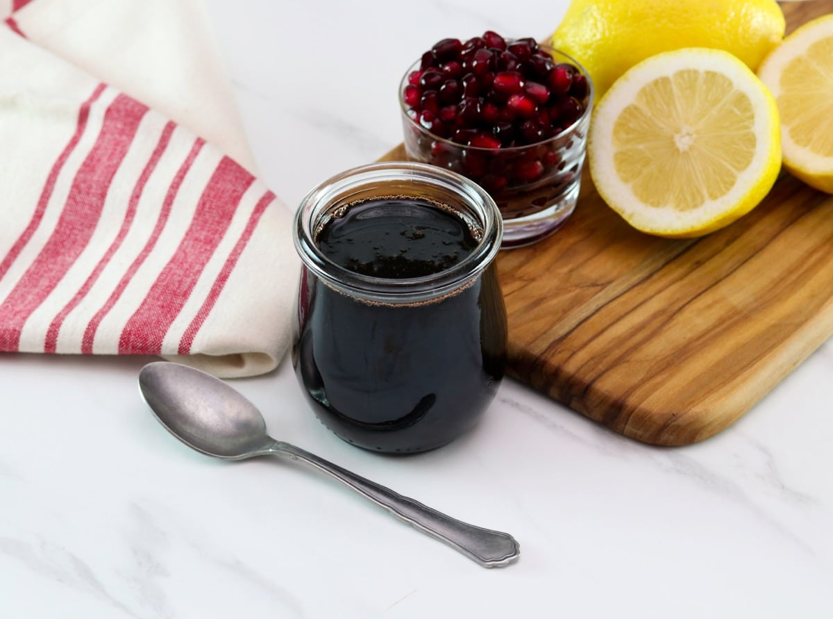 Horizontal shot of a small glass jar filled with pomegranate molasses sitting next to a cutting board holding sliced lemons and a dish of pomegranate arils.