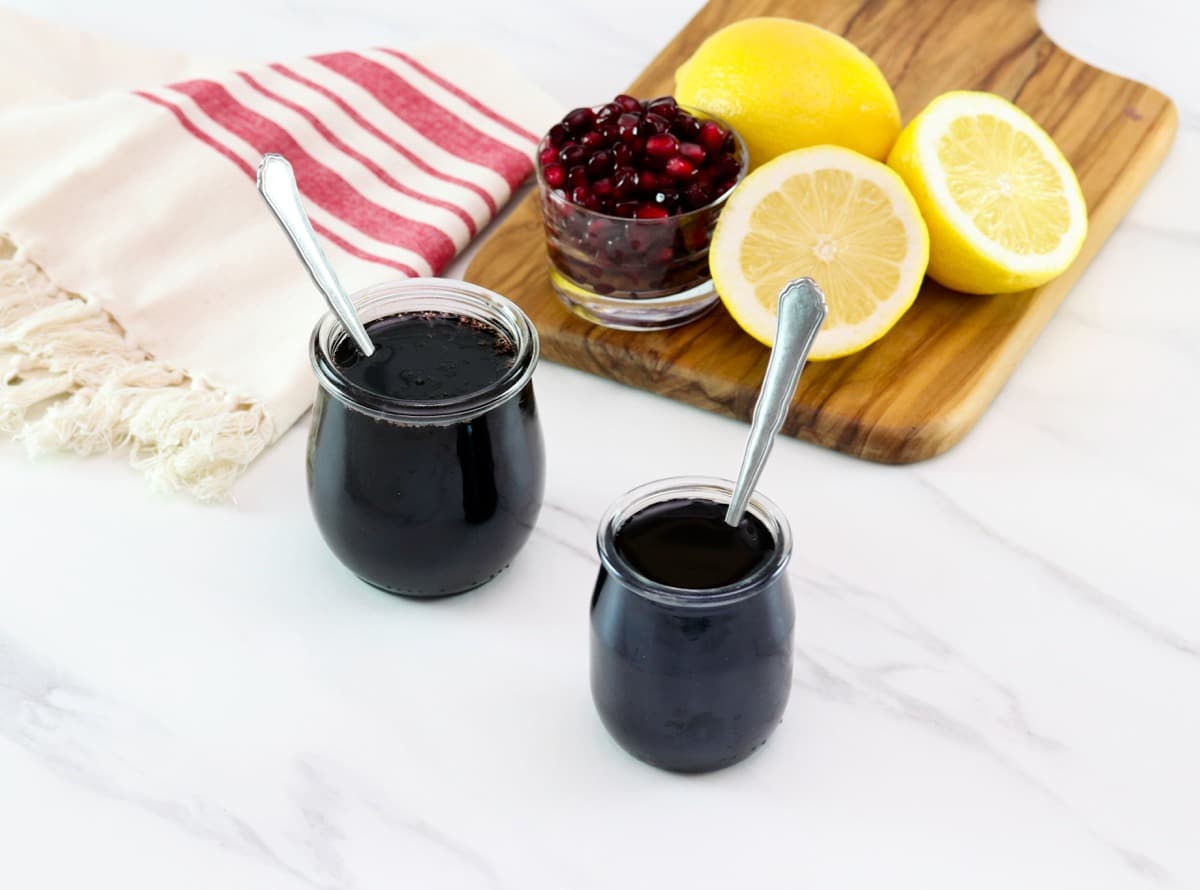 Horizontal shot of two glass jars filled with pomegranate molasses next to a cutting board holding sliced lemons and pomegranate arils.