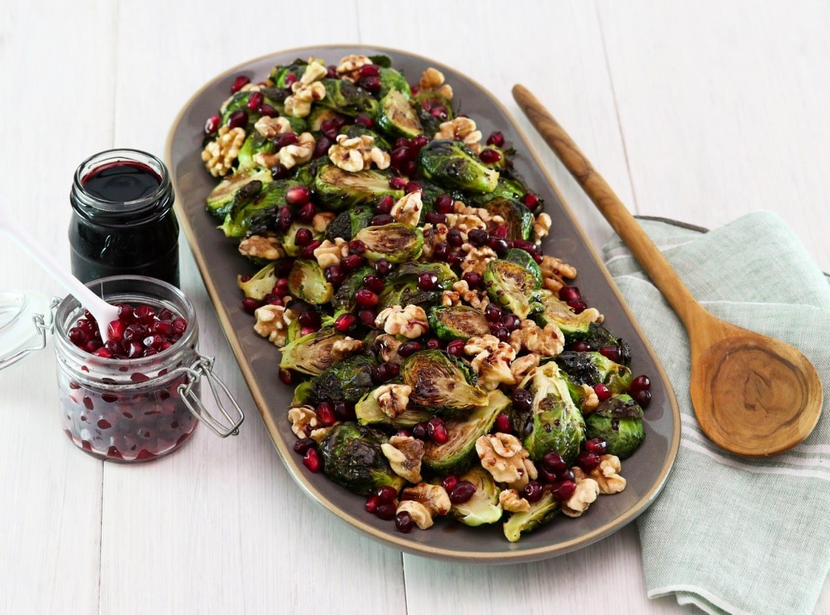 Horizontal shot of a platter filled with roasted brussels sprouts topped with pomegranate molasses.