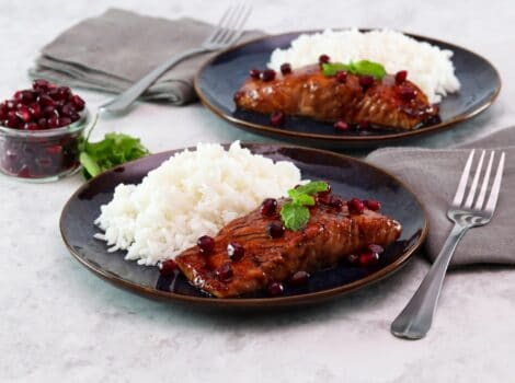 Horizontal shot of two plates holding pomegranate glazed salmon next to a serving of white rice.