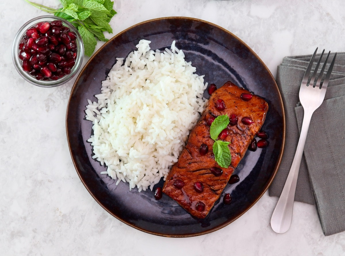 Overhead shot of a plate containing a fillet of pomegranate glazed salmon next to a serving of white rice.