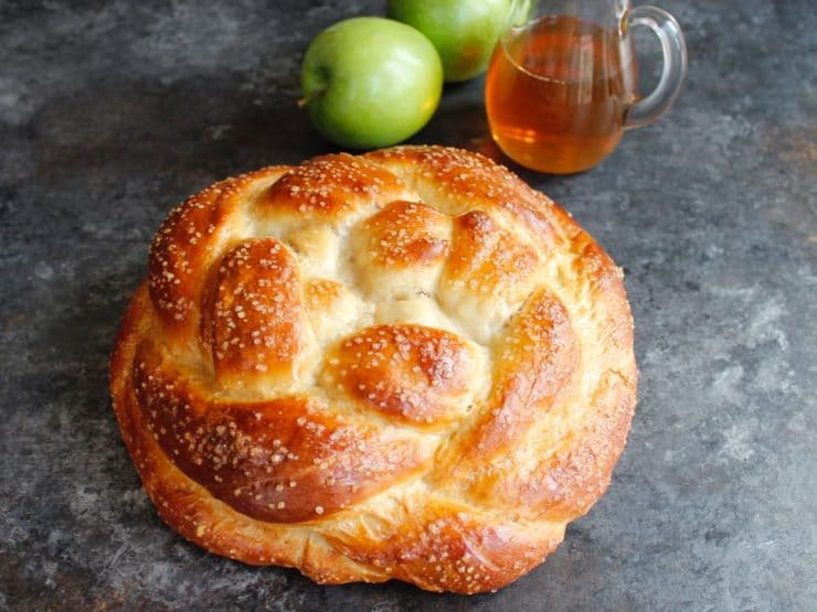 Round braided Apple Honey Challah with sparkling sugar coating on concrete background with two green apples and glass carafe of honey.