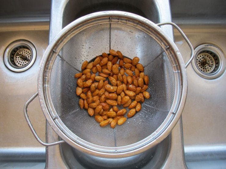 Overhead shot of wet almonds draining in mesh strainer colander.
